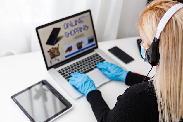 Compras online durante a quarentena de coronavírus. mulher com máscara protetora em casa, espaço livre