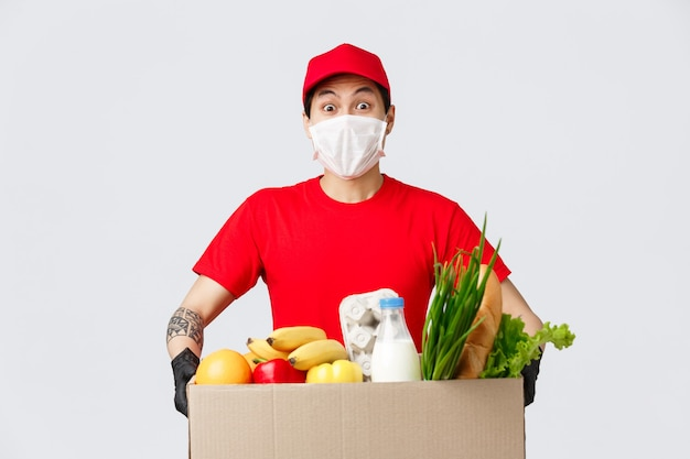 Compras online, entrega de comida e conceito de pandemia de coronavírus. entregador asiático amigável com máscara médica e luvas, segurando um pacote com mantimentos frescos, correio traz produtos para o cliente