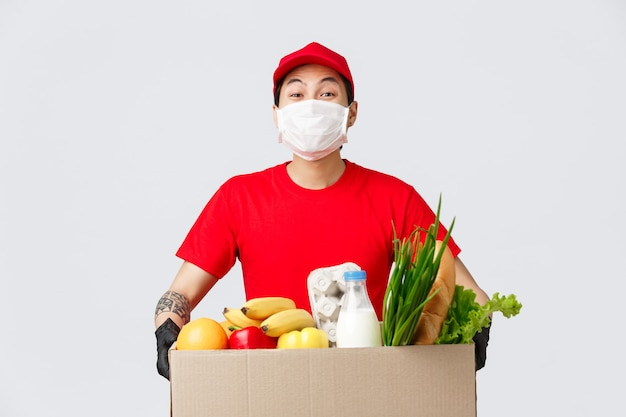 Compras online, entrega de comida e conceito de pandemia de coronavírus. entregador sorridente de uniforme vermelho, segurando uma caixa com mantimentos frescos, usar máscara médica e luvas, fazer compras sem contato