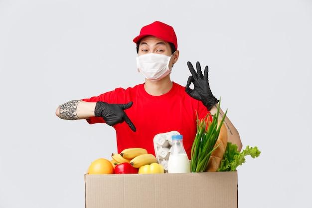 Compras online, entrega de comida e conceito de pandemia de coronavírus. excelente serviço de correio prestado por entregador asiático, mostrar sinal de bom garantia de qualidade, apontar pacote com mantimentos, usar máscara
