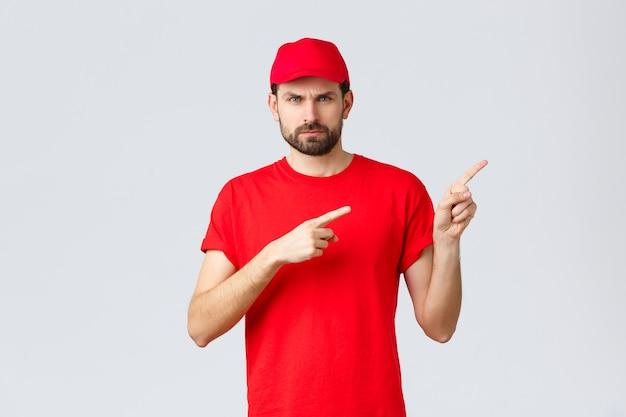 Compras online, entrega durante a quarentena e conceito de take-away. correio descontente e zangado com boné e camiseta do uniforme vermelho, carrancudo mal-humorado, apontando os dedos para a direita em desaprovação, sentindo-se incomodado