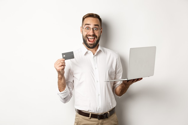 Compras online. homem bonito, mostrando o cartão de crédito e usando o laptop para fazer um pedido na internet, em pé