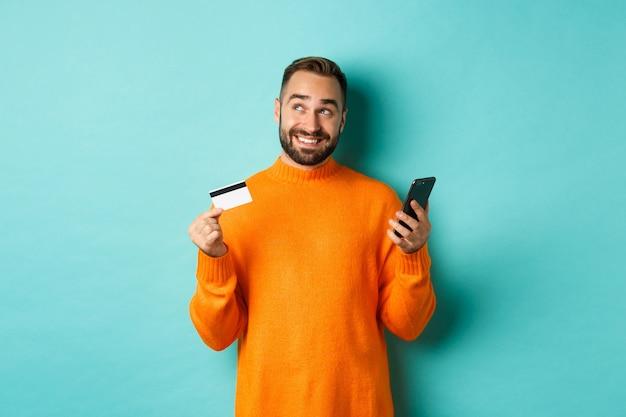 Compras online. homem bonito, pensando, segurando o smartphone com cartão de crédito, pagando na loja da internet, em pé sobre a parede turquesa clara.