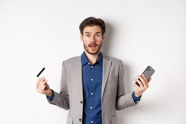 Compras online. homem confuso de terno espalhou as mãos para os lados, segurando um cartão de crédito de plástico com o telefone celular e encolhendo os ombros, parado no fundo branco.