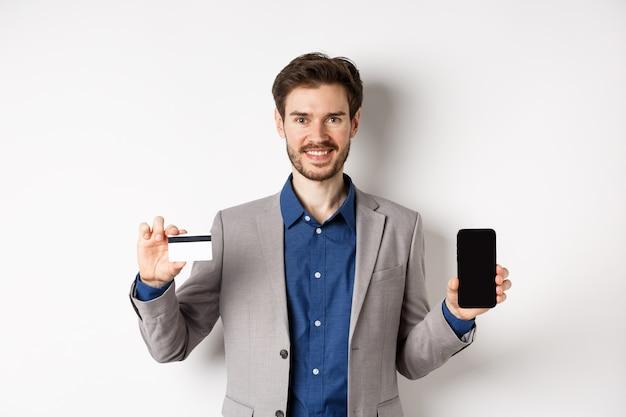 Compras online. homem de negócios sorridente de terno mostrando o cartão de crédito de plástico com tela vazia do smartphone, de pé contra um fundo branco.