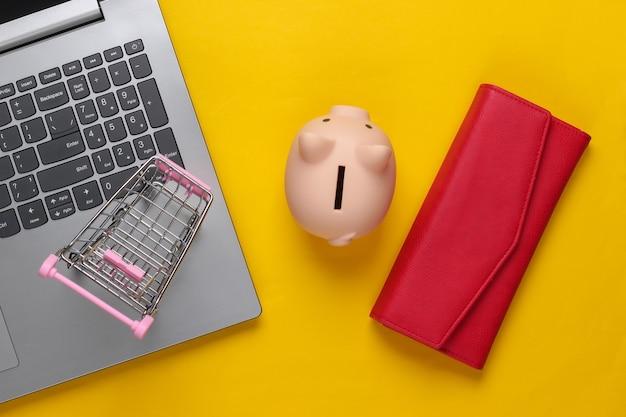Compras online. laptop com cofrinho, carrinho de supermercado, carteira em amarelo