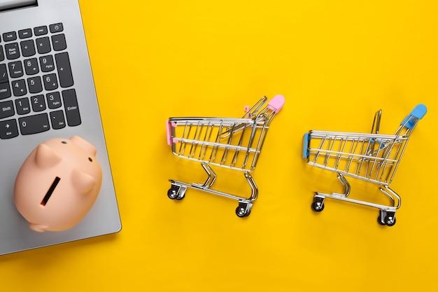Compras online. laptop com cofrinho, carrinho de supermercado em amarelo