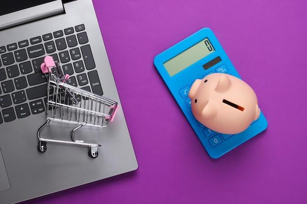Compras online. laptop com cofrinho, carrinho de supermercado em roxo