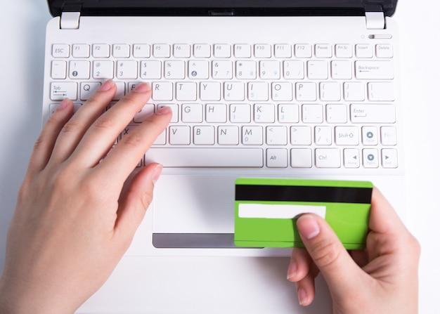 Compras online - mãos femininas com cartão de crédito e teclado de laptop