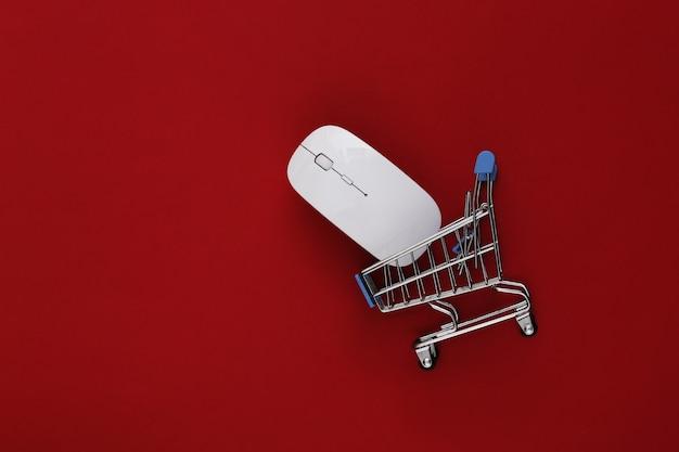Compras online. mouse do pc e mini carrinho de compras com relógio sobre fundo vermelho. vista do topo. postura plana