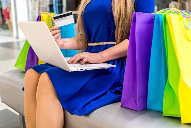 Compras online, mulher em shopping com laptop e cartão