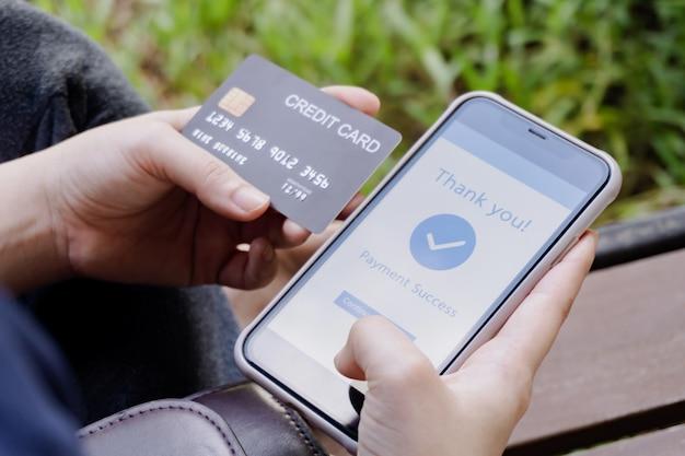 Compras online, pagamento móvel. mulher com as mãos segurando um cartão de crédito e usando um telefone inteligente para pagamento online