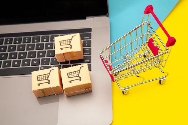 Compras online - papelão ou pacote de papel com o logotipo de um carrinho de compras em um teclado de laptop