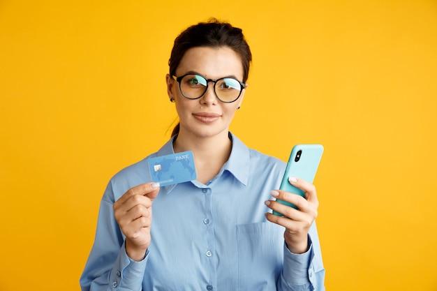 Compras online por telefone. mulher com celular e cartão de crédito no estúdio isolado.