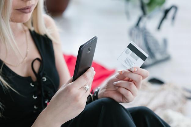 Compras online. tecnologia moderna conveniente. pagamentos móveis e conceito fácil de compra de mercadorias. mulher segurando smartphone e cartão de crédito nas mãos.
