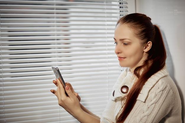 Compras online, uma jovem pesquisando as mercadorias da loja online na tela do smartphone.