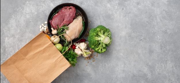Compras sacola com vista superior de alimentos saudáveis em um espaço de cópia de concreto