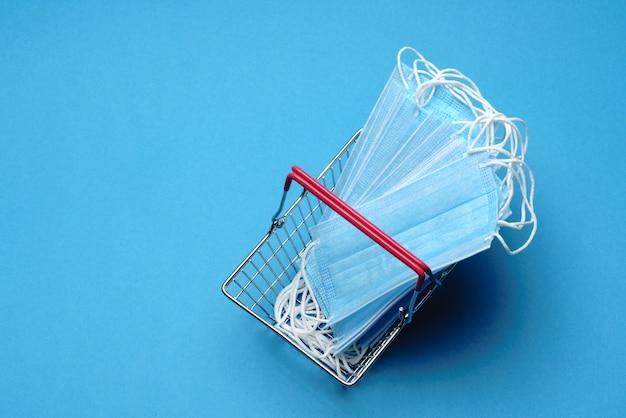 Compras seguras e on-line no conceito de quarentena. cesto de compras com máscara médica protetora sobre fundo azul