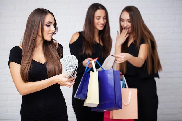 Compras. três mulheres segurando sacolas coloridas no feriado de sexta-feira preta
