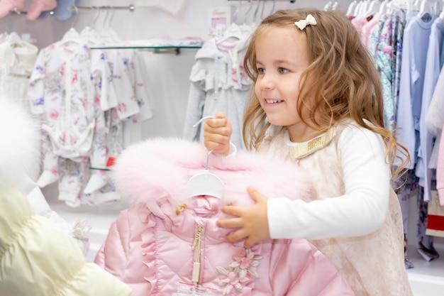 Compras. uma garota encantada com segurando uma jaqueta