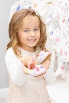 Compras. uma garota escolhe sapatos para o vestido.