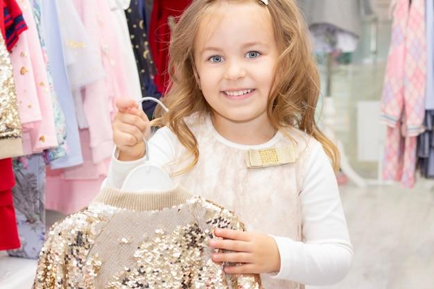 Compras. uma garota experimentando uma linda blusa no provador de uma boutique.