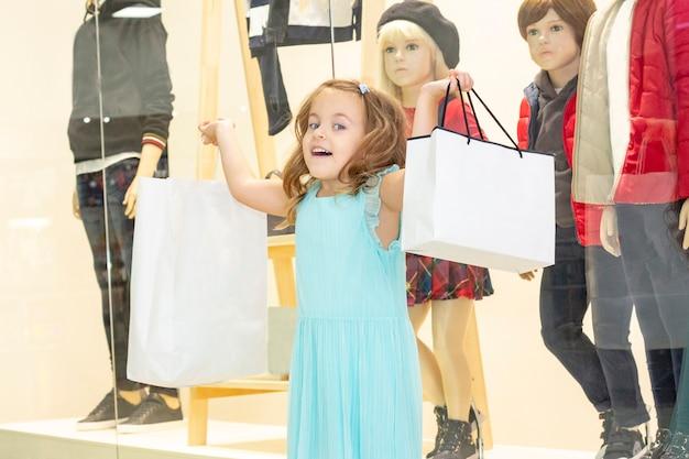 Compras. uma menina com sacolas de compras nas mãos.