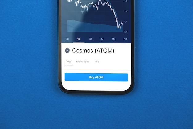 Compre a criptomoeda cosmos atom pelo aplicativo para celular, conceito de comércio online, investimento e troca de moedas com smartphone, foto comercial e financeira