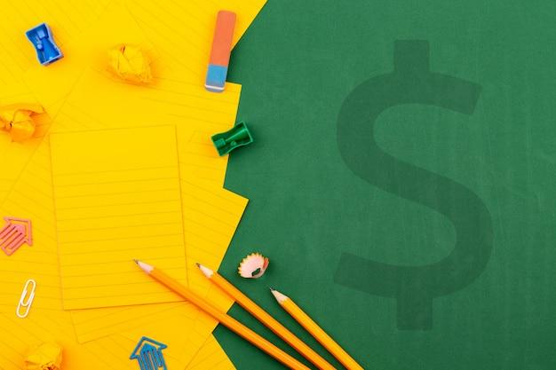 Compre a ilustração dos artigos de papelaria da escola com sinal de dólar e a folha de papel alaranjada na placa de escola verde. perto de lápis e páginas amarrotadas. copie o espaço flat lay vista superior conceito educação