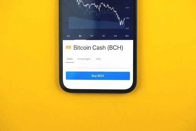 Compre bitcoin cash bch criptomoeda por aplicativo de telefone móvel, conceito de comércio online, investimento e troca de moedas com smartphone, foto comercial e financeira