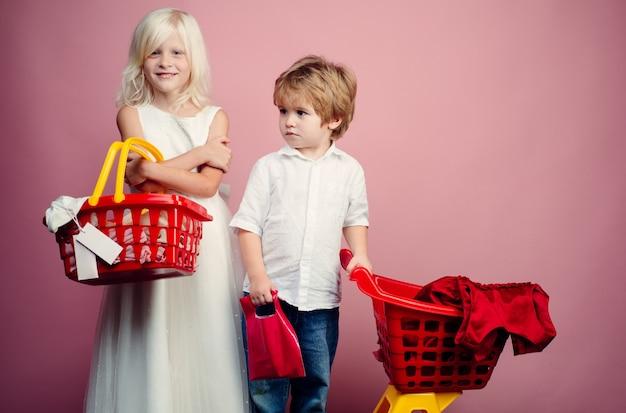 Compre com desconto. crianças de menina e menino às compras. crianças de casal segurando brinquedo de cesta de compras de plástico. loja para crianças. shopping center. compre produtos. jogue o jogo da loja. cliente cliente bonito do comprador segura o carrinho de compras.