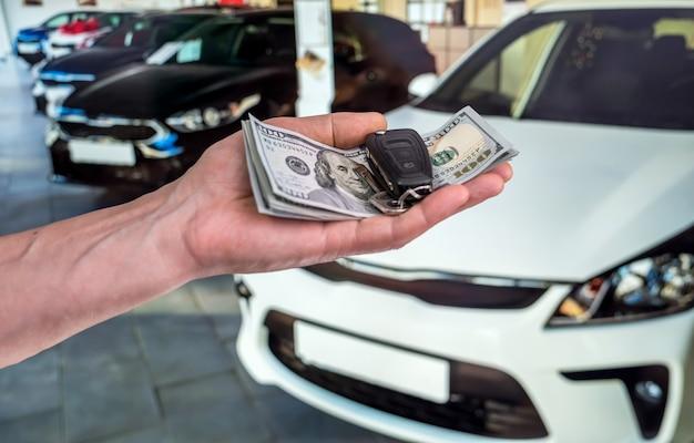 Compre ou alugue um carro novo. mão com o dinheiro do dólar e as chaves do carro. finança
