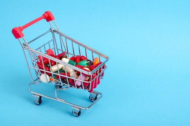 Compre remédios, cesta de compras com vários medicamentos, pílulas, comprimidos sobre fundo azul.