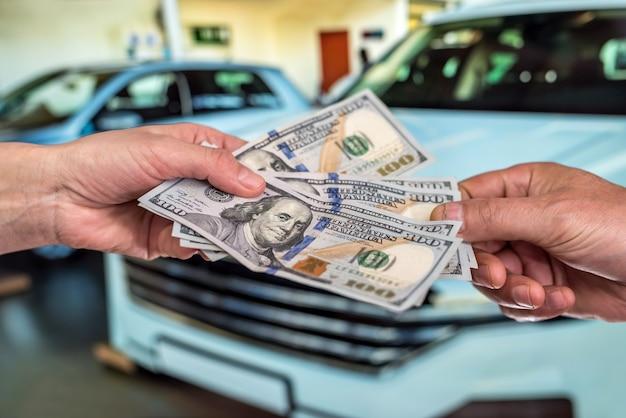 Compre um novo conceito de acr. homem segurando dólar para alugar automóvel. finança