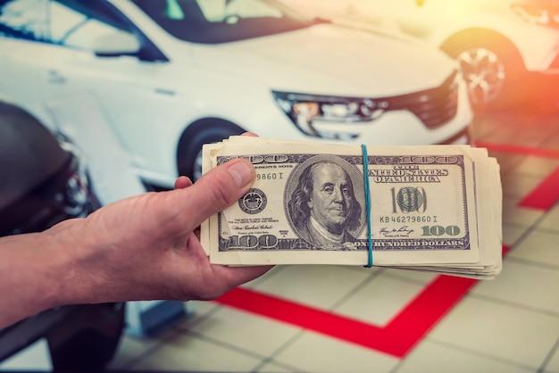 Compre um novo conceito de acr. homem segurando dólar para aluguel de automóveis. finança