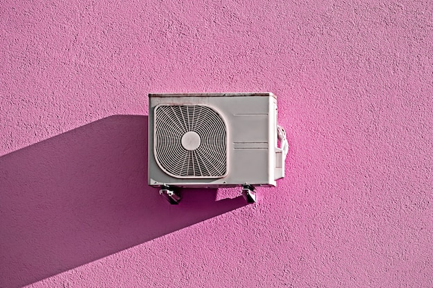 Compressor de ar condicionado moderno na parede grunge rosa com sombra