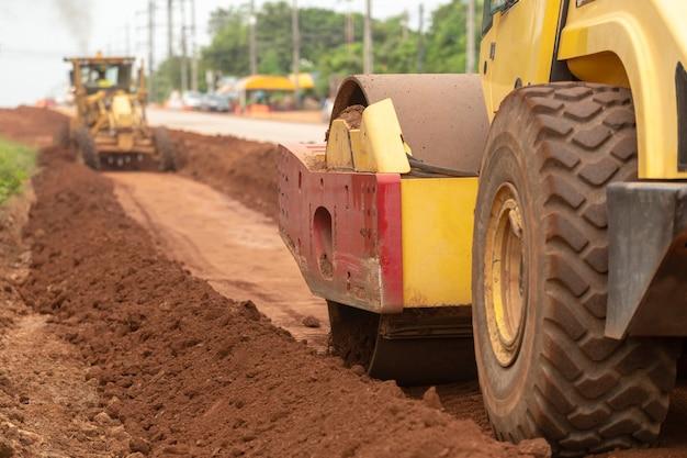 Compressor vibratório amarelo do solo que trabalha no canteiro de obras da estrada.