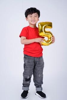 Comprimento de corpo inteiro de criança asiática sorriso feliz com balão de papel alumínio, isolado