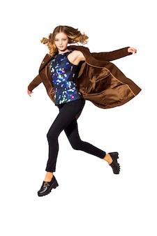 Comprimento total a jovem garota de cabelos compridos pulando no estúdio. isolat