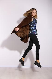 Comprimento total a jovem garota de cabelos compridos pulando no estúdio