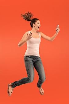Comprimento total da bela jovem pegando o telefone enquanto pula contra o fundo vermelho do estúdio.