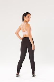 Comprimento total da jovem garota asiática focada e motivada com corpo magro perfeito, treinando na academia, olhando por trás, vista traseira da atrevida desportista virar para a câmera, fundo branco.