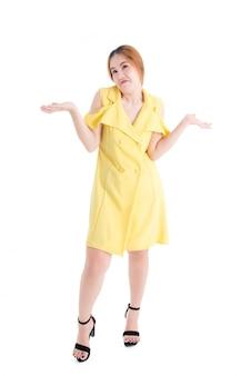 Comprimento total da menina asiática em vestido amarelo mostrando expressões faciais para desconsiderar certas coisas no whiteground branco