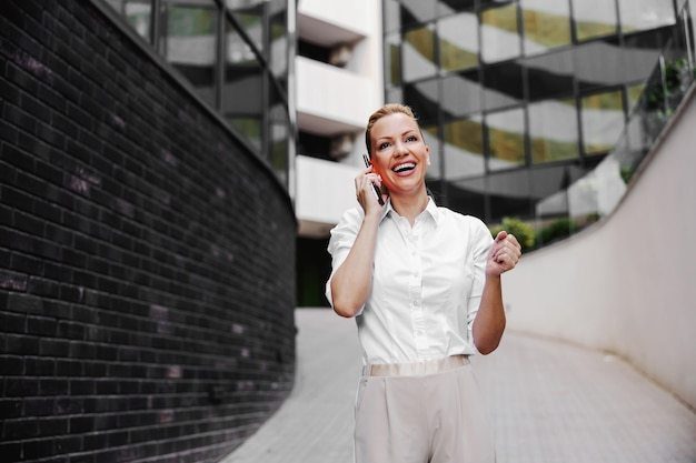Comprimento total da mulher de negócios loira atraente na moda falando ao telefone no exterior do centro de negócios.