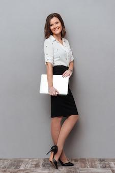 Comprimento total da mulher sorridente em roupas de negócios posando com computador tablet e olhando para a câmera. vista lateral