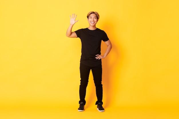 Comprimento total de amigável homem bonito asiático acenando com a mão em olá, sorrindo e dizendo oi sobre a parede amarela.