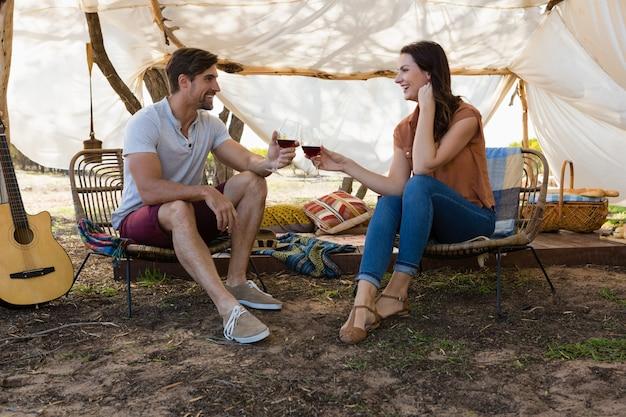 Comprimento total de casal brindando vinho na tenda