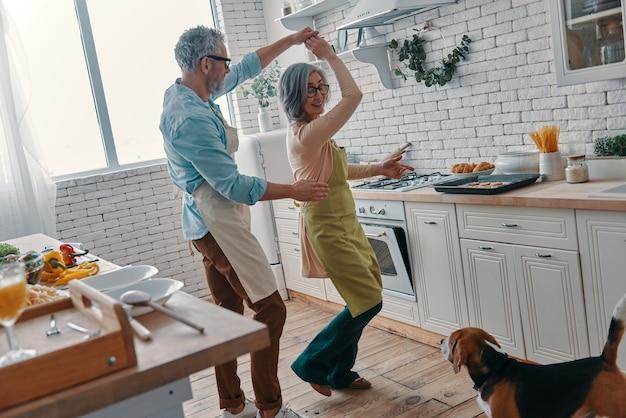 Comprimento total de casal sênior de aventais dançando e sorrindo enquanto prepara um jantar saudável em casa