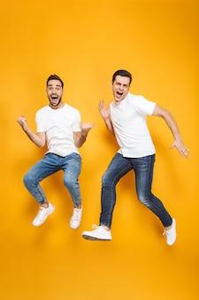 Comprimento total de dois amigos homens alegres e animados, vestindo camisetas em branco, pulando isolados sobre a parede amarela, comemorando