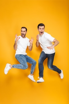 Comprimento total de dois amigos homens alegres e animados, vestindo camisetas em branco, pulando isolados sobre a parede amarela, ok
